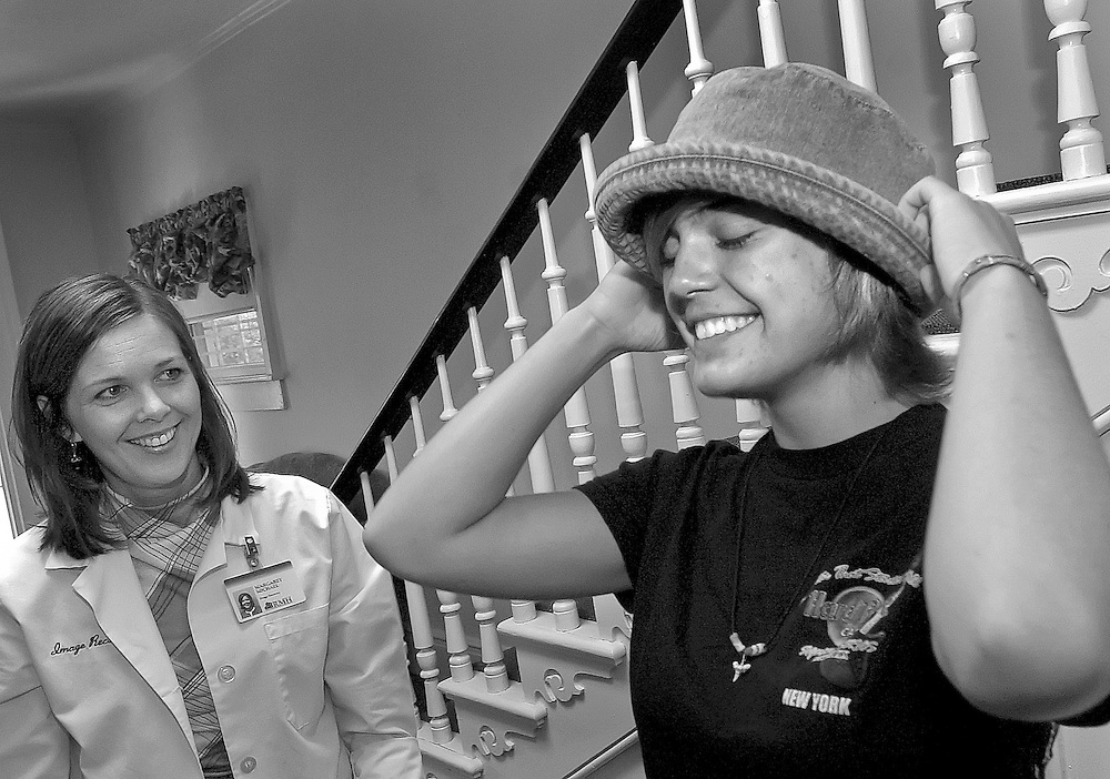 Margaret Michael, director of the RMH Image Recovery Center, looks on as Alyssa tries on hats that she may want to wear when her hair begins to fall out from the chemo treatments.