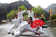 Asia, China, Hubei province. A group of martial arts students posing in postures of Woudang mountain style martial arts on a platform over Drangon Spring lake on Wudang moutain (Wudang-san), a World Heritage mountain with many Taoist monasteries.