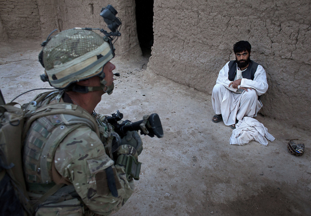 British soldiers of 16 Air Assault Bde's elite BRF (Brigade Reconnaissance Force) question a local mad as they move from compound to compound searching for weapons and explosives as part of an operation in the Western Dasht, Helmand Province, Southern Afghanistan on the 18th of March 2011.