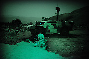 A german major on a nightpatrol using his &quot;LUCIE&quot; nightscpope to look for insurgents and TAliban after the PRT was attacked the night before with rockets. in the background a german fuks van.A Major from the German ISAF forces take aim at a possible Taliban position in the mountains outside Faizabad. the night prior the PRT in Faizabad was attacked with several rockets. ISAF and ANA go out on regular patrols to search for insurgents who are attacking frequently in the northern part of Afghanistan. In the back , a german Fuchs with nightscope overlook the mountains.<br /> <br /> For more caption info, please contact photographer.