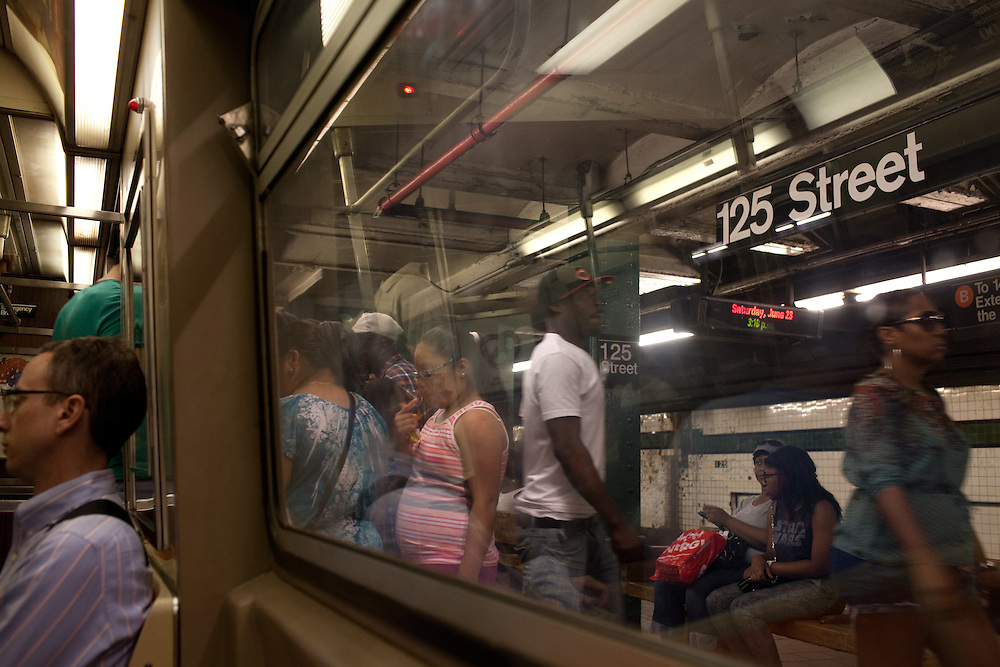 Commuters board the A train at 125 Street subway stop on June 23, 2012.