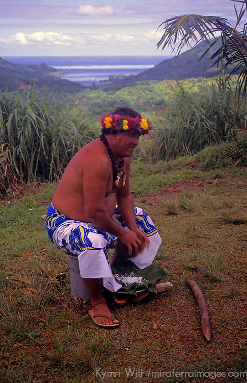 Oceania, South Pacific, French Polynesia, Tahiti. Tahitian islander demonstrates breaking a coconut.