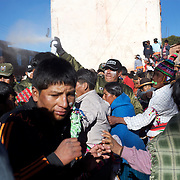Police use tear gas to disperse villagers as fighting gets out of control between rival villages during the Tinku Festival. Macha, Bolivia, 4th May 2010, Photo Tim Clayton ..Each May, up to 3000 thousands indigenous Bolivian indians descend on the isolated mountainous village of Macha 75 miles north of Potosi in the Bolivian Andes. The 600 year old pre-hispanic Bolivia Festival of Tinku sees villagers from all over the region march into town to be pitted against each other in a toe to toe fist to fist combat.. They dance and sing in traditional costume and drink 96% proof alcohol along with chicha, a fermented beverage made from corn. Townspeople and sometimes the police oversee proceedings who often use tear gas to try and control the villages, whipped into a fighting frenzy by the dancing and alcohol, but as the fiesta goes on things often escalate beyond their control, with pitched battles between rival villages break out,  The blood spilt is an offering to the earth goddess - Pachamama - to ensure a good harvest for the coming year. Over the years dozens have died, yet the rite continues.