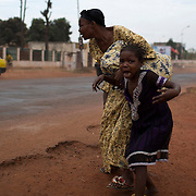 A mother holds her child while attempting to take cover as repeated gun shots are heard close to Miskine district during continuing sectarian violence in the capital Bangui.