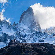 """Mount Fitz Roy (3405 meters or 11,170 feet) rises abruptly above native forest in the southern Andes mountains, near El Chaltén village, in Los Glaciares National Park, Argentina, South America. In 1877, explorer Perito Moreno named """"Cerro Fitz Roy"""" for Robert FitzRoy (no space before the capital R) who, as captain of the HMS Beagle, had travelled up the Santa Cruz River in 1834 and charted much of the Patagonian coast. First climbed in 1952 by French alpinists Lionel Terray and Guido Magnone, Mount Fitz Roy has very fickle weather and is one of the world's most challenging technical ascents. It is also called Cerro Chaltén, Cerro Fitz Roy, and Monte Fitz Roy (with a space before the R). Chaltén comes from a Tehuelche (Aonikenk) word meaning """"smoking mountain"""" (explained by frequent orographic clouds). Cerro is a Spanish word meaning hill. El Chaltén village was built in 1985 by Argentina to help secure the disputed border with Chile, and now tourism supports it, 220 km north of the larger town of El Calafate. The foot of South America is known as Patagonia, a name derived from coastal giants, Patagão or Patagoni, who were reported by Magellan's 1520s voyage circumnavigating the world and were actually Tehuelche native people who averaged 25 cm (or 10 inches) taller than the Spaniards. Mount Fitz Roy is the basis for the Patagonia company's clothing logo, after Yvon Chouinard's ascent and subsequent film in 1968. Panorama stitched from 4 overlapping photos."""