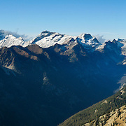 This view from the top of Carne Mountain into Glacier Peak Wilderness Area includes: Buck Mountain (left), Glacier Peak, Liberty Cap, Fortress Mountain (middle left), Chiwawa Mountain (middle), Spider Gap, Sevenfingered Jack (sharp peak on right) and Mount Maude (with white glacier to its right). Phelps Ridge runs from the lower left to the middle of this image, with Phelps Creek Valley in front of it, and the Chiwawa River Valley behind. (Panorama stitched from 8 images.) Hike 7 miles 3600 feet to top of Carne Mountain (elevation 7085 feet). This panorama was stitched from 8 images.
