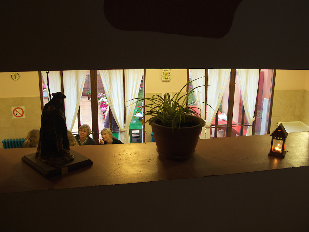 Pilgrims chat over the dinner table. A statue of Saint James, a plant and a lamp sit in the space in the wall separating the kitchen from the stairs.