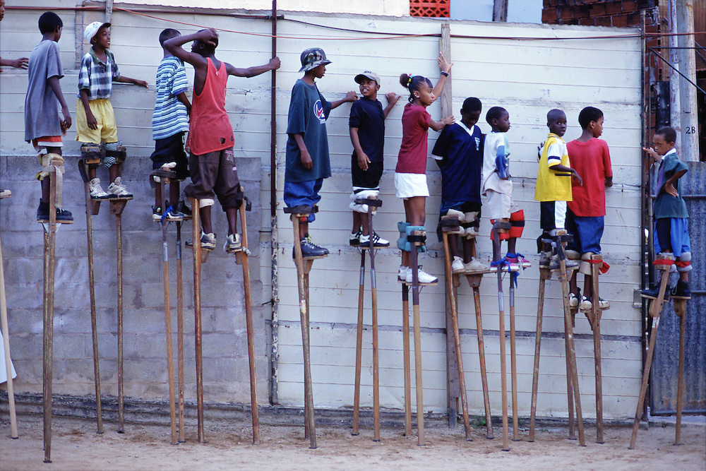 "Trinidad and Tobago ""MOKO JUMBIES: The Dancing Spirits of Trinidad"".(Moko Jumbies line up to walk outside the yard and practice on different road surfaces.).A photo essay about a stilt walking school in Cocorite, Trinidad..Dragon Glen de Souza founded the Keylemanjahro School of Art & Culture in 1986. The main purpose of the school is to keep children off the streets and away from drugs..He first taught dances like the Calypso, African dance and the jig with his former partner Cathy Ann Samuel.  Searching for other activities to engage the children in, he rediscovered the art of stilt-walking, a tradition known in West Africa as the Moko Jumbies , protectors of the villages and participants in religious ceremonies. The art was brought to Trinidad by the slave trade and soon forgotten..Today Dragon's school has over 100 members from age 4 and up..His 2 year old son Mutawakkil is probably the youngest Moko Jumbie ever. The stilts are made by Dragon and his students and can be as high as 12-15 feet. The children show their artistic talents mostly at the annual Carnival, which today is unthinkable without the presence of the Moko Jumbies. A band can have up to 80 children on stilts and they have won many of the prestigious prizes and trophies that are awarded by the National Carnival Commission. Designers like  Peter Minshall , Brian Mac Farlane and Laura Anderson Barbata create dazzling costumes for the school which are admired by thousands of  spectators. Besides stilt-walking the children learn the limbo dance, drumming, fire blowing and how to ride  unicycles..The school is situated in Cocorite, a suburb of Port of Spain, the capital of Trinidad and Tobago..all images © Stefan Falke"