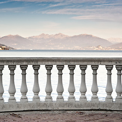 A classical column banister faces the tranquil waters of Lake Maggiore in Italy