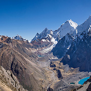"Cordillera Huayhuash panorama from San Antonio Pass (5000 meters or 16,4000 feet) includes left to right: pyramidal Yerupaja Grande (center, 6635 m or 21,770 ft, highest peak in the Amazon basin); Nevado Serapo with Siula Grande (6344 m or 20,800 ft) rising behind; and Nevado Carnicero (5960 m). Below is turquoise lake Juraucocha at 4343 m. This photo is from Day 6 of our 9 days trekking in 2014 around the Cordillera Huayhuash in the Andes Mountains, Peru, South America. With a severely broken leg in 1985, climber Joe Simpson crawled for 3 days alone over 5 miles down this hazardous glacier back to his empty camp in the Sarapococha Valley (center). The gripping 2003 British docudrama ""Touching the Void"" captures the account told in Joe's 1988 book, ""Touching the Void: The True Story of One Man's Miraculous Survival."" After climbers Joe Simpson and Simon Yates scaled the treacherous Siula Grande, Joe broke his leg, and their descent became one of the most amazing survival stories in mountaineering history. This panorama was stitched from 8 overlapping photos."