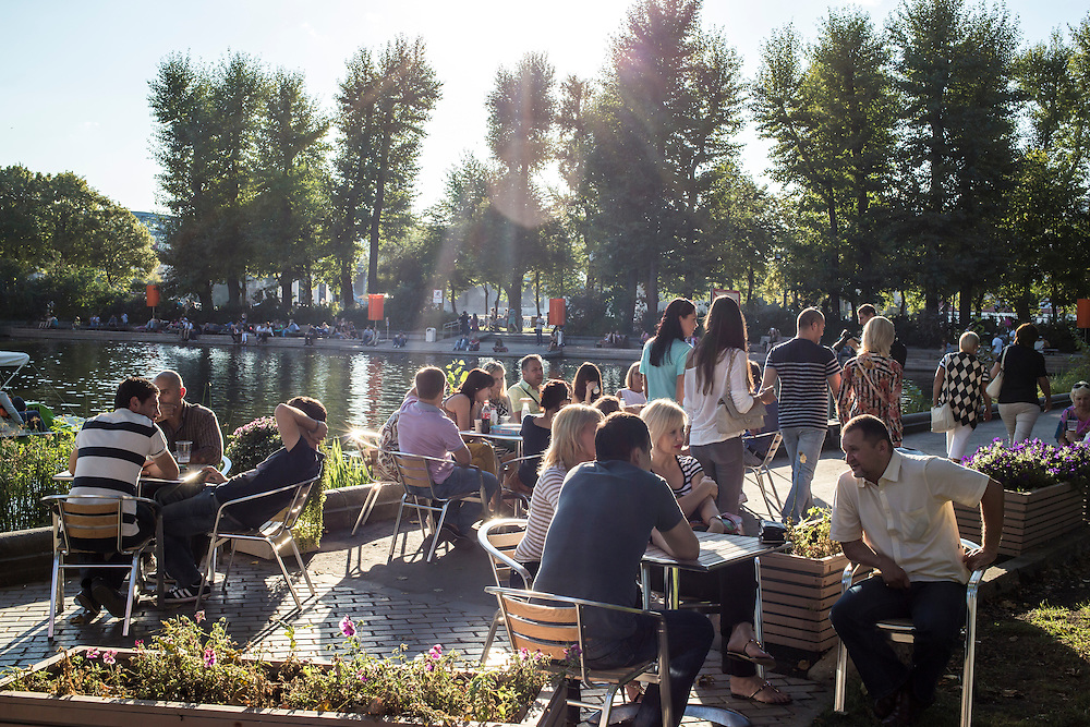People sit at a cafe next to Golitsinsky Pond in Gorky Park on Saturday, August 17, 2013 in Moscow, Russia.