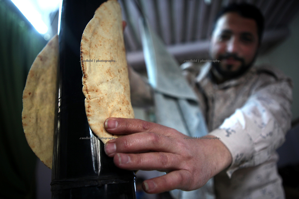 A Free Syrian Army Soldier warms up a flat bread at a hot stove chimney in Al Janoudiyah, Province of Idlib, Syria.