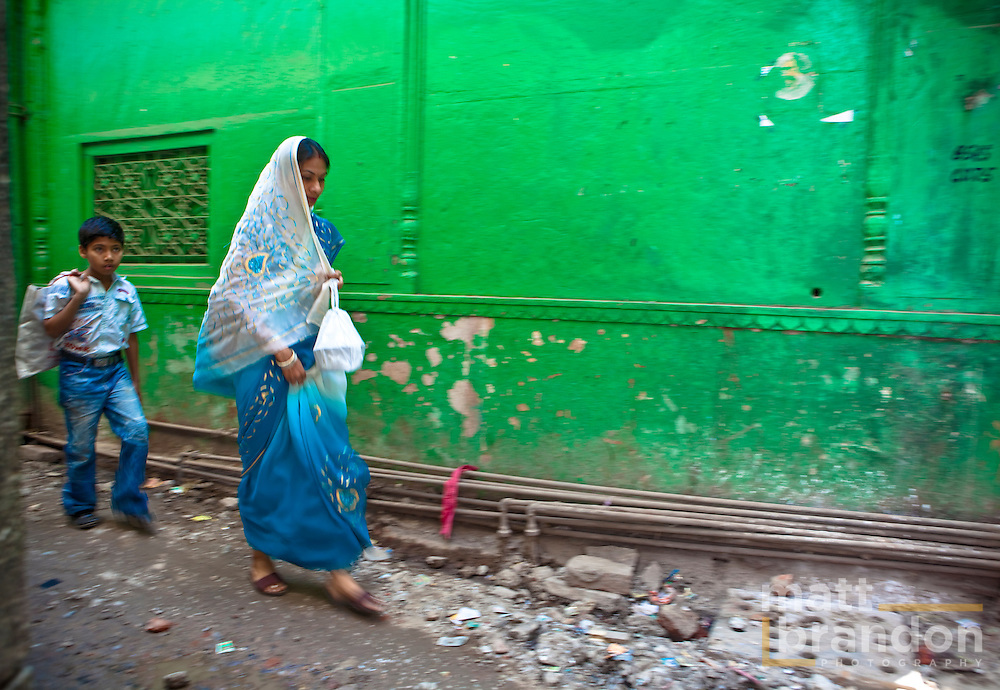 A woman in a blue sari walks in front of a green wall in the back alleyways of old Delhi.