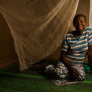Ami Ouedraogo (21) with her mosquito net in the village of Songodin in the Sanmatenga region of Burkina Faso on 25 February 2014. Mosquito nets greatly decrease the incidence of malaria by reducing the risk of being bitten by the nocturnal Anopheles mosquito, which carries the malaria parasite.
