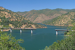 Digitally Altered Damaged Bridge with Missing Section of Road Under Construction by Don Pedro Lake, California, USA