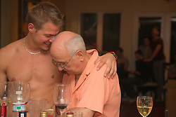 shirtless man at a party with an older man