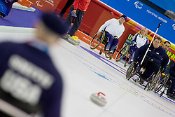 PINEROLO, ITALY - MARCH 15th : Held steady by team mate James Joseph, team USA skipper Jim Pierce plays a stone during the last round robin match of the men's curling between Great Britain and the USA during Day 5 of the Turin 2006 Winter Paralympic Games on March 15th, 2006 at the Pinerolo Palaghiaccio Stadium in Turin, Italy. (Photo by George S. Blonsky)