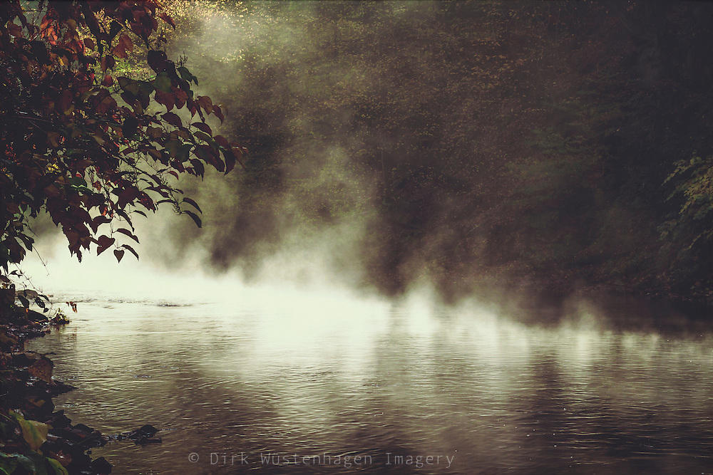 Sun meeting river - rising fog on a fall morning