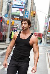 man in a tank top walking in New York City