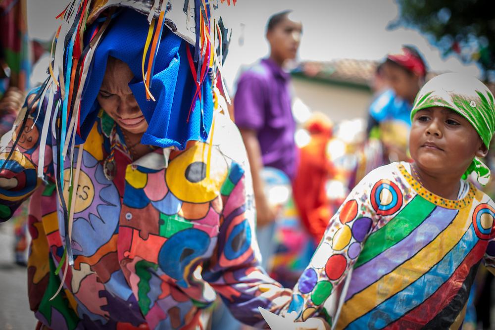 Un mujer junto a su hijo paga promesa durante la festividad del Corpus Christi, representada en Venezuela a traves del ritual magico-religioso de los Diablos Danzantes. Los Diablos de Naiguata se identifican por pintar sus propios trajes y decorarlos con cruces, rayas y circulos, figuras que impiden que el maligno los domine. Las mascaras son en su gran mayoria animales marinos. Llevan escapularios cruzados, crucifijos y cruces de palma bendita. Naiguata, 30 Mayo 2013. (ivan gonzalez)