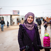 "Imur, 17, from Dara'a, Syria is along the infamous market street, ""Champs-Élysées"" in Zaatari camp for Syrian refugees, Jordan, 2014."