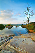 """Near the Cradle of Humankind World Heritage Site (where the 2.3-million year-old fossil Australopithecus africanus - nicknamed """"Mrs. Ples"""" - was found in 1947), a Highveld summer sunset is reflected in the pond of a pure spring near Tonquani Kloof in the ancient quartzites of the Magaliesberg mountain range northwest of Johannesburg.  This area has been occupied by humans for more than 2 million years.  The range itself has a much longer geological history that began as sedimentary deposits that were later consolidated and tilted under the forces of a massive upwelling of molten magma.  This view is to the north.  South Africa. Nikon F4, 28-70/3.5-4.5D. Kodak EPP."""