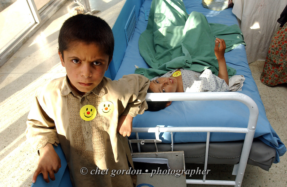 """A young Afghan boy pauses by the bedside of a fellow patient in the Orthopedic Chidren's Ward of the Indira Ghandi Children's Hospital in Kabul on Friday, May 24, 2002. The Geshundheit Instititute, founded by Dr. Hunter """"Patch"""" Adams, Lufthansa Cargo, and DHL Worldwide Express collaborated to ship medicines, food and orthopedic supplies to the Indira Ghandi Children's Hospital, clinics and orphanages in Kabul. The German NGO (Non Governmental Organization) Hammer Forum supervised the distribution of the donated supplies from various non-profit organizations in the U.S. and The Netherlands."""