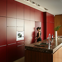 Red kitchen units with kitchen island and women walking through door