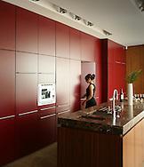 Red kitchen units with kitchen island and women walking through door