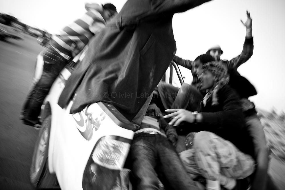 Des combattants rebelles emmènent un blessé en pick-up après un bombardement de l'armée loyaliste, le 25 mars 2011 à une dizaine de kilomètres de la ville d'Aj Dabiya tenue par les forces Kadhafistes.