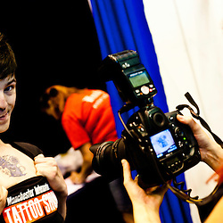 Manchester, UK - 5 August 2012: a visitor with a brand new tattoo poses for a photographer during the Manchester Tattoo Show, one of the most popular conventions of the UK tattoo community.
