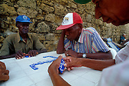 Cuatro hombres mayores disfrutan de una partida de domino. Con unas coloridas piezas azules, sobre una mesa junto a la muralla, se distraen. Mientras protegen sus caras del sol, con sus gorras. Cartagena de Indias, 2001 (Ramón Lepage / Orinoquiaphoto)     The fortified wall of Cartagena is in excellent condition and stretches more-or-less unbroken round a good portion of the Old Town. It is a pleasure for locals well as visitors to walk and observe the colonial architecture and excellent view of the Caribbean ocean..