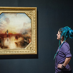 London, UK - 8 September 2014: a gallery assistant poses next to 'War: The Exile and Rock Limpet exhibited 1842' by J.M.W. Turner, during the press preview of The EY Exhibition: Late Turner – Painting Set Free exhibition at Tate Britain