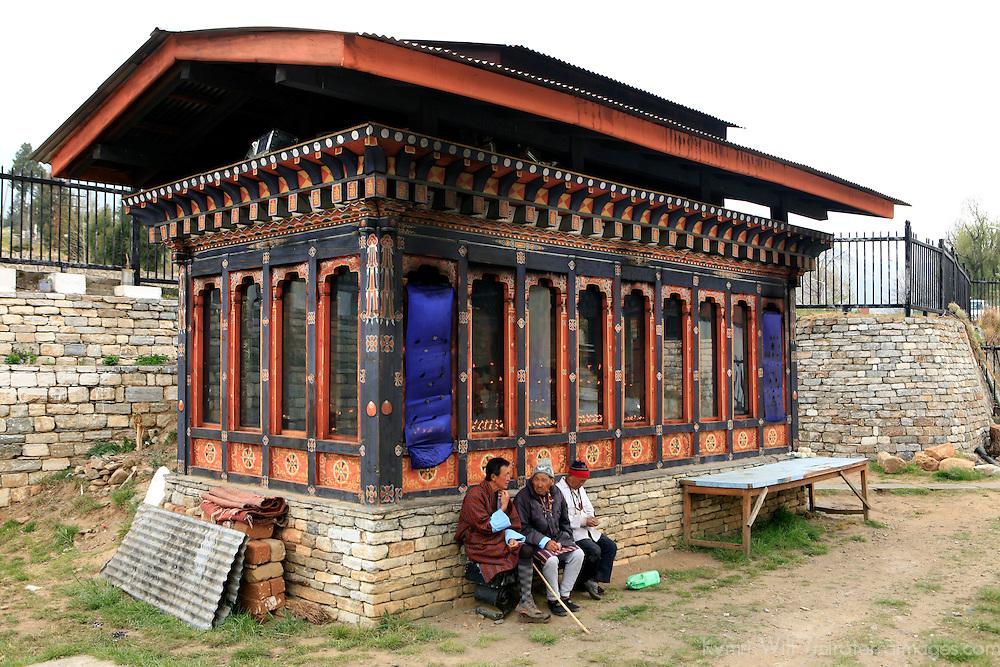 Asia, Bhutan, Thimpu. Three men sit nearby the Memorial Chorten in Thimpu.