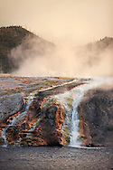 The sun sets behind the Firehole River and Midway Geyser Basin in Yellowstone National Park.