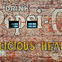 Drink Pepsi Cola for Delicious Health Wall Advertisement in Durham, North Carolina<br /> On the side of the Durham Co-op Grocery building in North Carolina is this faded advertisement for Pepsi Cola. When the product started in a North Carolina drug store in 1892, it was called, &ldquo;Brad&rsquo;s Drink.&rdquo; Its current name is derived from pepsin - a digestive enzyme - and kola nuts. This slogan &ldquo;Delicious Health&rdquo; started in 1909 when a car racing pioneer became the first celebrity endorser. The advertising phrase was used for another twenty years.