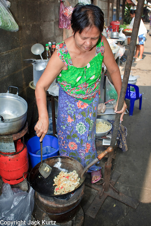 """Mar. 21, 2009 -- BANGKOK, THAILAND:  A food vendor prepares her lunch stand in a narrow alley in the Monk's Bowl Village. The Monk's Bowl Village on Soi Ban Baat in Bangkok is the only surviving one of what were originally three artisan's communities established by Thai King Rama I for the purpose of handcrafting """"baat"""" the ceremonial bowls used by monks as they collect their morning alms. Most monks now use cheaper factory made bowls and the old tradition is dying out. Only six or seven families on Soi Ban Baat still make the bowls by hand. Most of the bowls are now sold to tourists who find their way to hidden alleys in old Bangkok. The small family workshops are only a part of the """"Monk's Bowl Village."""" It is also a thriving residential community of narrow alleyways and sidewalks.     Photo by Jack Kurtz"""