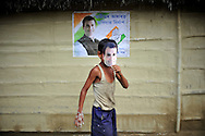A boy wearing a mask of congress party candidate Rahul Gandhi hangs campaign posters near a polling station during the second phase of voting in parliamentary elections April 23, 2009 in the Muslim dominated town of Mukalmua in the state of Assam, India.  Congress party leaders Rahul Gandhi and Kamal Nath, the commerce minister, and key government allies face Indian voters today in the second round of polling in a five-stage general election.