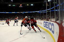 Mar 30, 2007; East Rutherford, NJ, USA; New Jersey Devils center Travis Zajac (19) skates around Philadelphia Flyers defenseman Derian Hatcher (2) during the third period at Continental Airlines Arena in East Rutherford, NJ.