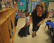 Kindergarten teacher Mandy James helps student Za-Nijen Hickinbottom find his cubby for his backpack on the first day of school at Bramlett Elementary in Oxford, Miss. on Thursday, August 4, 2011.  (AP Photo/Oxford Eagle, Bruce Newman)