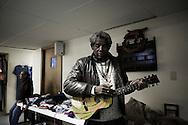 "OHIO, Toledo, October 27, 2012:  A man testing a used practice guitar inside the basement of the ""Primera Iglesia Bautista"". ALESSIO ROMENZI"