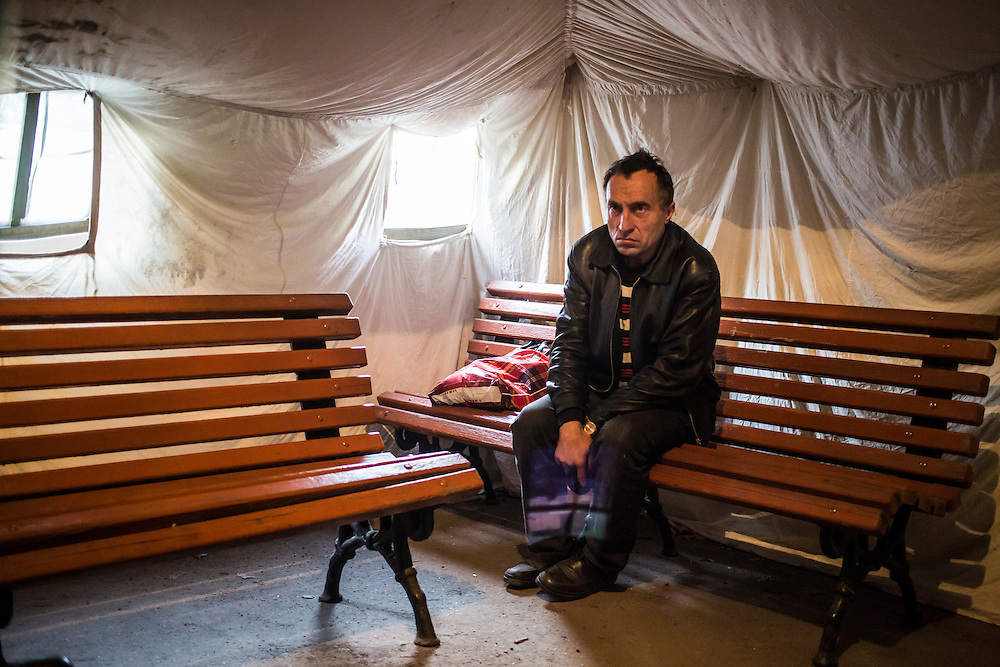DNIPROPETROVSK, UKRAINE - OCTOBER 11: A man waits in a tent for the opening of a center to help people displaced by fighting in Ukraine's East on October 11, 2014 in Dnipropetrovsk, Ukraine. The United Nations has registered more than 360,000 people who have been forced to leave their homes due to fighting in the East, though the true number is believed to be much higher. (Photo by Brendan Hoffman/Getty Images) *** Local Caption ***