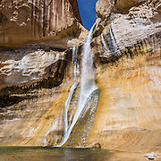 Hike Lower Calf Creek Falls trail 6 miles round trip (600 feet gain), in Grand Staircase Escalante National Monument, Utah, USA. The beautiful cascade drops 126 feet (38 meters) from sandstone cliffs stained with fascinating patterns of desert varnish. Directions: From the town of Escalante, drive 15 miles east on Scenic Byway 12 to Calf Creek Recreation Area day-use parking and campground. More about desert varnish: Manganese-rich desert varnish requires thousands of years to coat a rock face that is protected from precipitation and wind erosion. The varnish likely originates from airborne dust and external surface runoff, including: clay minerals, oxides and hydroxides of manganese (Mn) and/or iron (Fe), sand grains, trace elements, and usually organic matter. Streaks of black varnish often occur where water cascades over cliffs, but wind doesn't sculpt its shape. Varnish color varies from shades of brown to black. Manganese-poor, iron-rich varnishes are red to orange, and intermediate concentrations are shaded brown. Manganese-oxidizing microbes may explain the unusually high concentration of manganese in black desert varnish, which can be smooth and shiny where densest. The panorama was stitched from 3 overlapping photos.