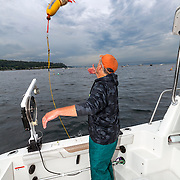 WA11840-00...WASHINGTON - Phil Russell tosses out a buoy float to mark a shrimp pot in the Puget Sound.  ((MR# R8)