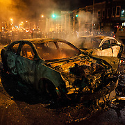 WASHINGTON, USA - APRIL 27: Police retreat from the hulks of burned out cars in the middle of an intersection during riots in Baltimore, USA on April 27, 2015. Protests following the death of Freddie Gray from injuries suffered while in police custody have turned violent with people throwing debris at police and media and burning cars and businesses.