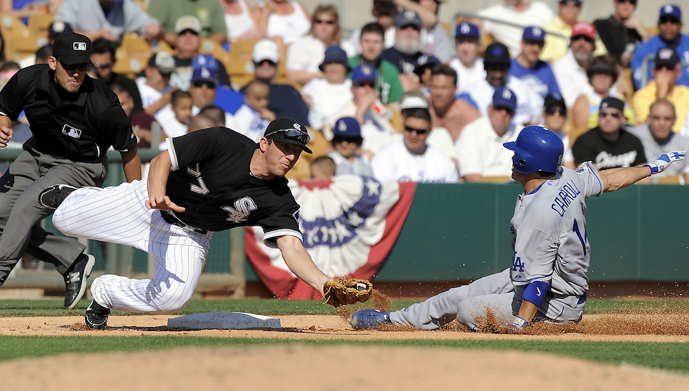 GLENDALE, AZ - MARCH 5:  Jamey Carroll #14 of the Los Angeles Dodgers steals third base avoiding the tag by Brent Morel #77 of the Chicago White Sox on March 5, 2010 at The Ballpark at Camelback Ranch in Glendale, Arizona. (Photo by Ron Vesely)