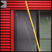 2016 OCTOBER 17 - Red corrugated metal wall with window. Photographed with Apple iPhone using Instagram App. By Richard Walker