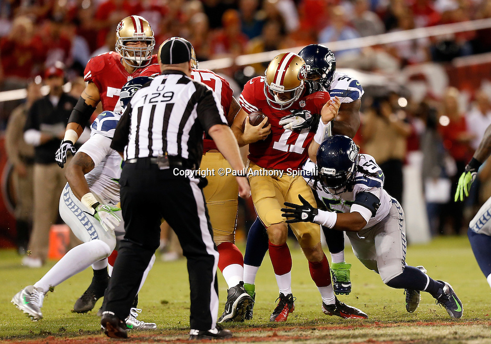 San Francisco 49ers quarterback Alex Smith (11) gets sacked by Seattle Seahawks defensive end Bruce Irvin (51) and a teammate during the NFL week 7 football game on Thursday, Oct. 18, 2012 in San Francisco. The 49ers won the game 13-6. ©Paul Anthony Spinelli