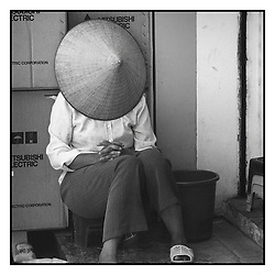 Hanoian woman sits on a small stool on a sidewalk with a conical hat over her face as she rests, Hanoi, Vietnam, Southeast Asia