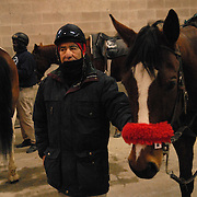 """Ernesto Cancino, 64, who has been a ponyboy who escorts the Thoroughbreds to the start at the Aqueduct racetrack in New York City since 1989, stands underneath the grandstand on a cold day, February 15, 2007. Before that he was a jockey in Chile, where he started riding horses on his father's farm at the age of 14. He says he loves the horses and the cold does not bother him, even half a century later. """"The body-I've got it ready all day,"""" he says. """"A little hot coffee, it's fine.""""..Betting on the horses is still a popular game and the money still flows, but off track betting and other forms of entertainment have eroded live attendance at the races.  The daily diehard betters and horse lovers who sparsely populate the place on work days are joined by a bigger crowd on the weekends. ..The Aqueduct, located in Ozone Park, Queens, is the only horse racing track in New York City and probably the coldest in the country (most of the others are in Kentucky, Florida or California). Horses race on the winterized inner dirt rack from January 1st through the end of April. Aqueduct was built in 1894, renovated in 1959, then opened for winter racing in 1975. It is the winter race track operated by the New York Racing Association (NYRA), which also runs Belmont and Saratoga in the warm seasons. Betters at Aqueduct watch and bet on the nine daily live races and all other races around the country via Simulcast. .."""